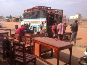Loading school furniture on vehicle ready to depart from Juba to Mundari Bura